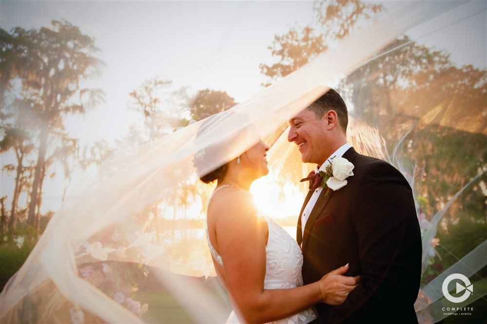 Bride and groom with draping veil in the wind