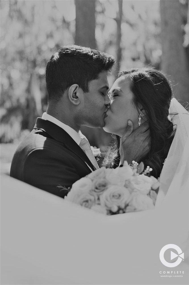 bride and groom kissing with floral bouquet