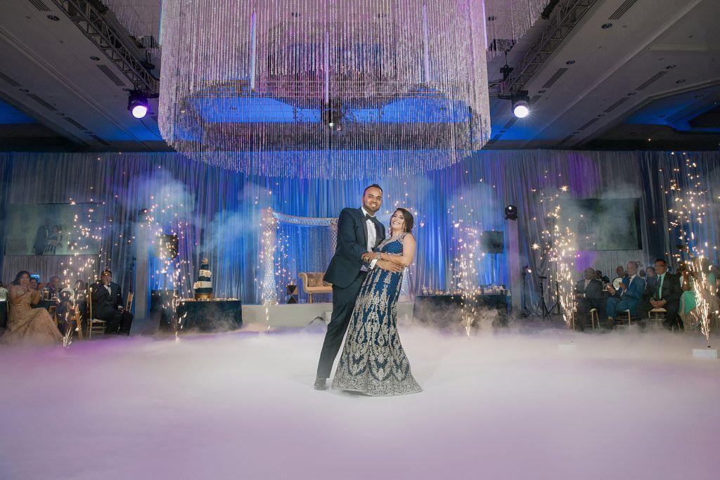 bride and groom under chandelier