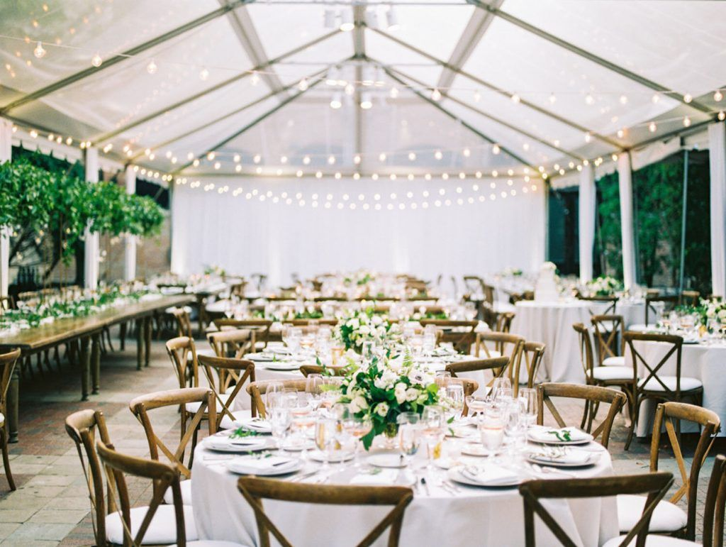 white reception set up with wooden chairs under lighted tent