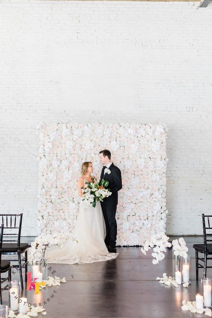 white flower wall with bride and groom