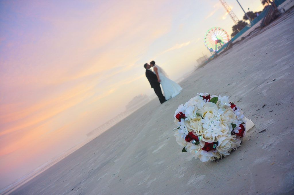 floral front with bride and groom on beach
