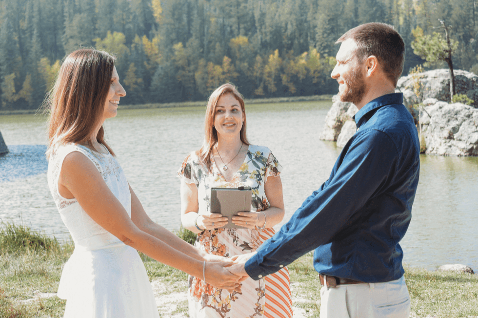 bride and groom with officiant in front of water