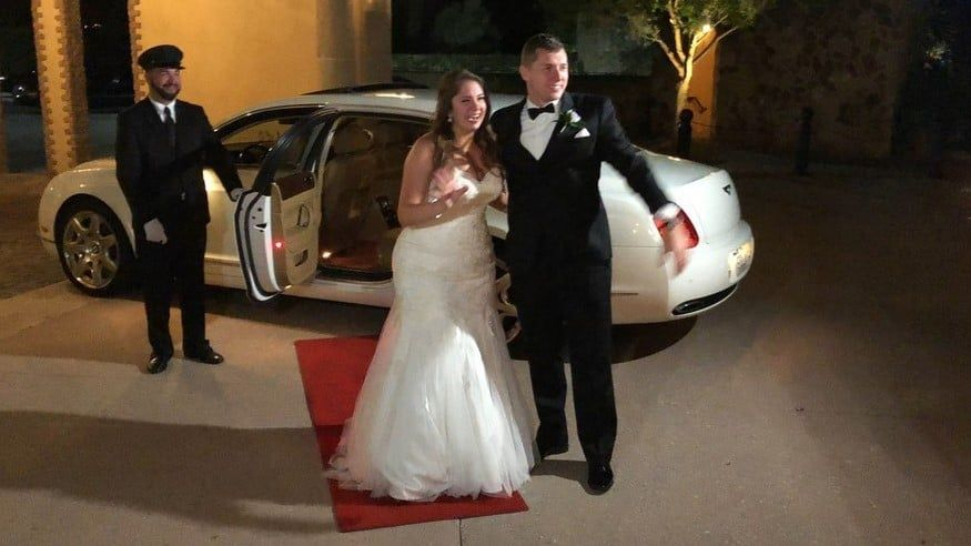 bride and groom on red carpet in front of limo