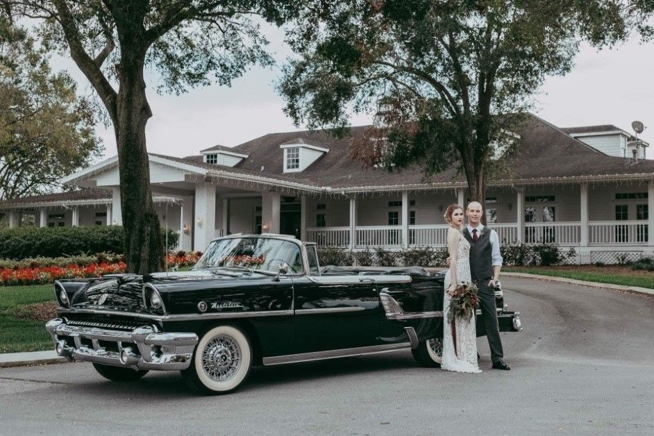 bride and groom in front of black classic car