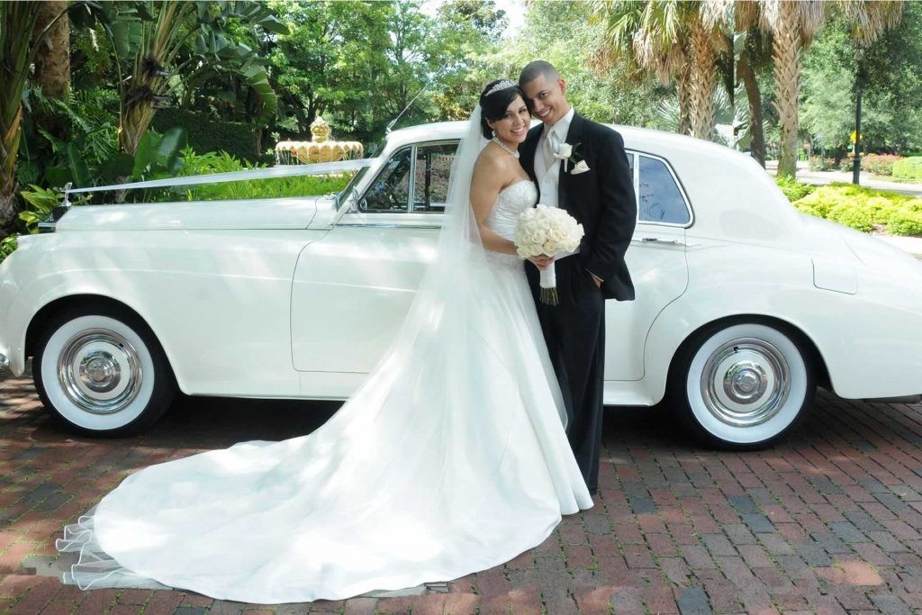 bride and groom in front of white limo