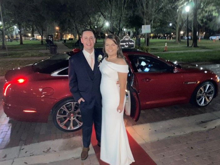 bride and groom in front of red classic car