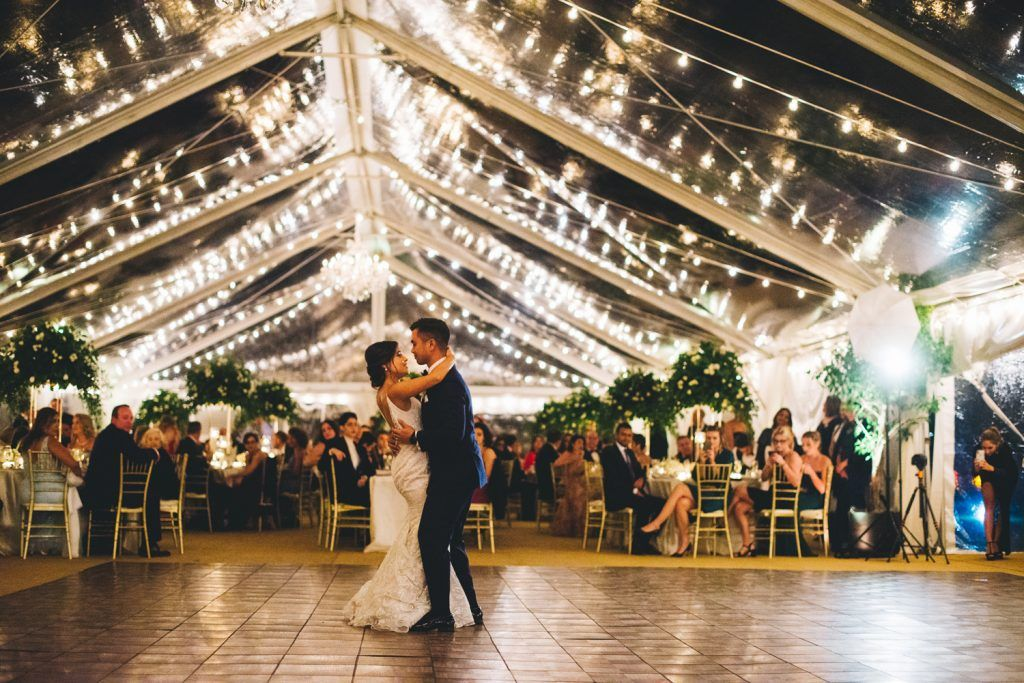 bride and groom dancing under market lights and tent