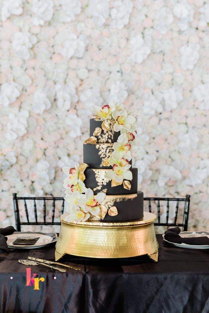 gold and black cake in front of white flower wall