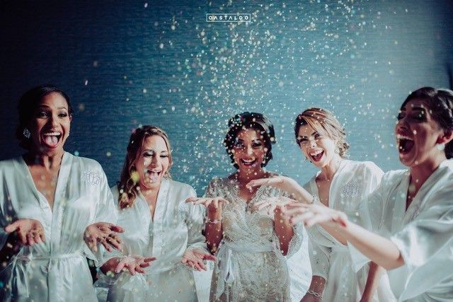 bride with bridesmaids throwing glitter