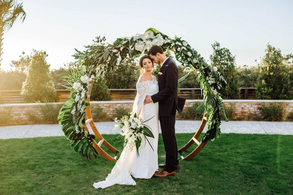 bride and groom in front of floral circle