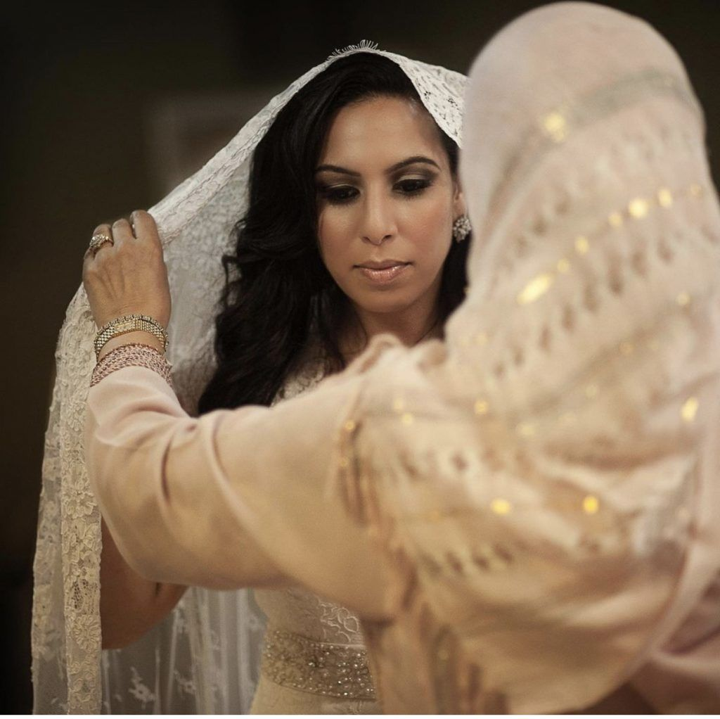 mother putting on brides veil