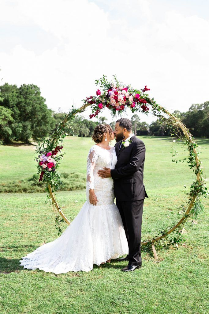 bride and groom in front of floral arch