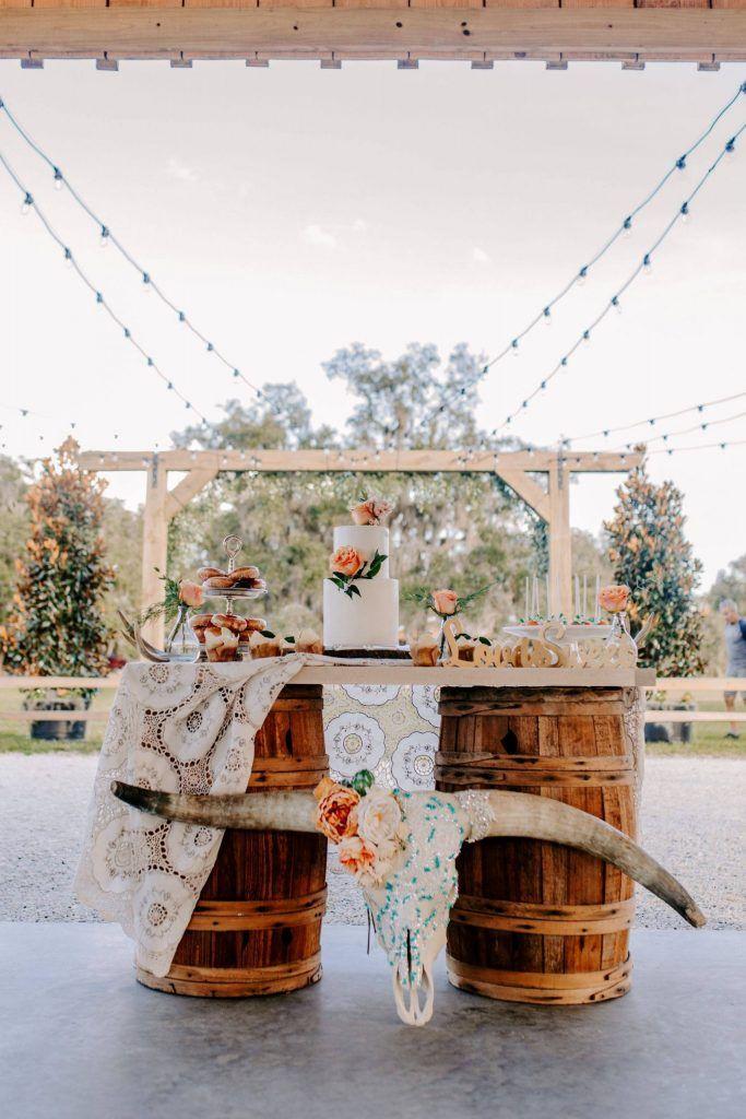 wedding cake on top of wooden barrels