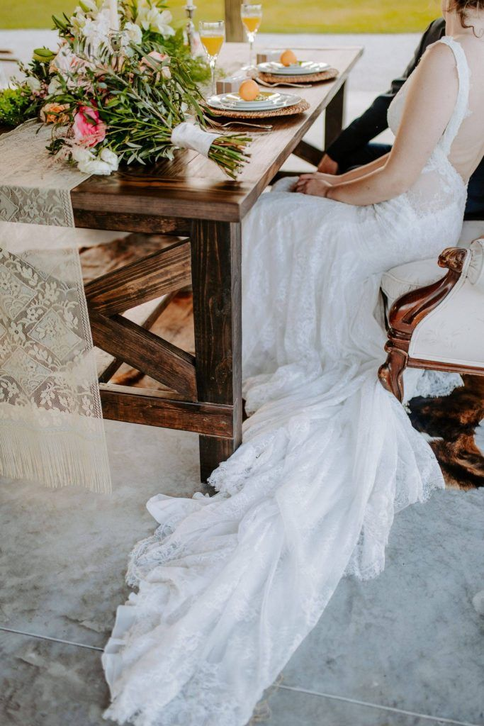 bride sitting at wooden reception table
