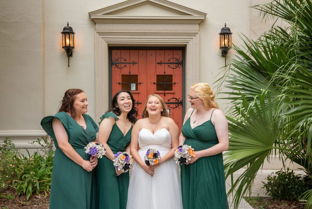 bride with bridesmaids wearing green dresses