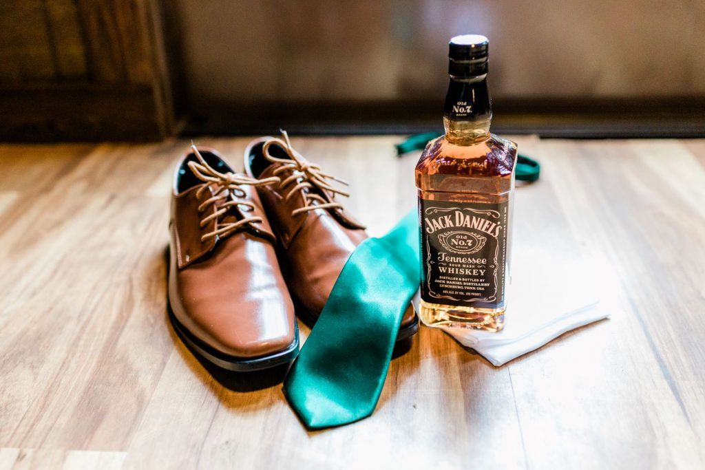 Groom's shoes and whiskey bottle