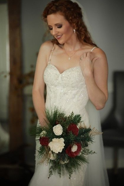 bride holding red and white roses bouquet